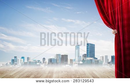 Human Hand Opens Red Velvet Curtain To Modern Cityscape And Cloudy Sky