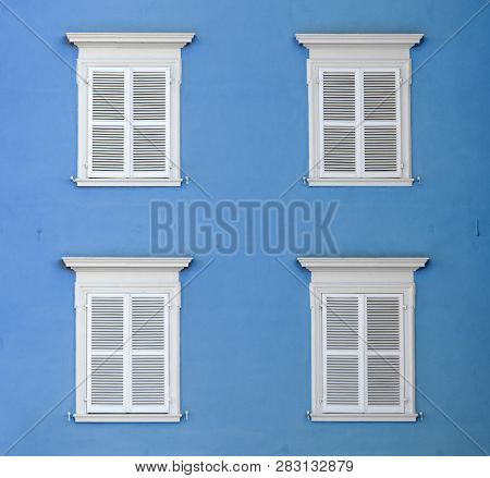 wooden shutter in white color with white wall gives a harmonic background poster