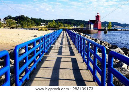 Holland Harbor Light, Big Red. Bright Blue Fences On The Pier, Behind The Pier Is The Turquoise Wate
