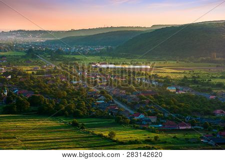 Countryside In Mountains Red Dusk In Springtime. Road To The Distant City Through Small Village In V