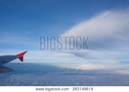 Wing Of Airplane Flying Above The Clouds .