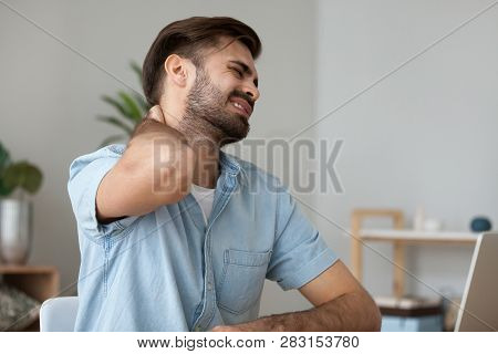 Upset Man In Pain Touching Stiff Neck Suffering From Fibromyalgia