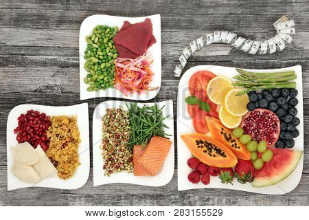 Super food for losing weight concept with fruit, vegetables, lean meat, fish, salads & tape measure, health foods high in antioxidants, anthocyanins, vitamins & dietary fibre. Flat lay on rustic wood.
