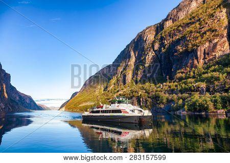 LYSEBOTN, NORWAY - AUGUST 14, 2018: Kolumbus ferryboat arriving to Lysebotn ferry terminal at the end of calm Lysefjord (Lysefjorden)