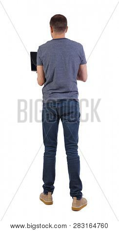 Back view of a man who is standing with a laptop. Rear view people collection.  backside view of person.  Isolated over white background. A student in a striped shirt standing standing in a laptop.