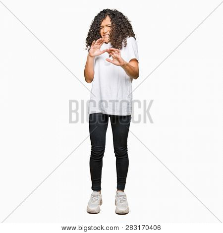 Young beautiful woman with curly hair wearing white t-shirt disgusted expression, displeased and fearful doing disgust face because aversion reaction. With hands raised. Annoying concept.
