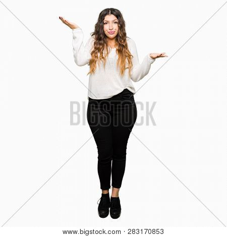 Young beautiful woman wearing white sweater clueless and confused expression with arms and hands raised. Doubt concept.