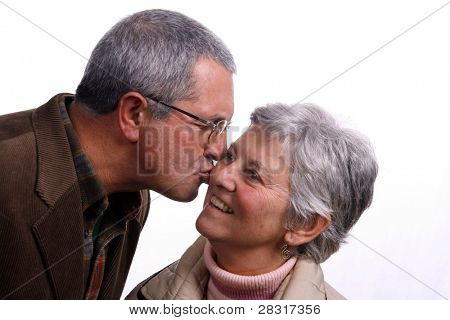 mature couple kissing over white background