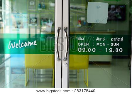 The Glasses Door With Thai Letters Means To Welcome And Open Time On Green Label At Car Repair Shop