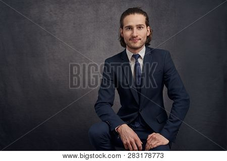 Handsome And Stylish Young Man With Long Hair, Wearing Fashionable Suit, Sitting On Bar Stool Agains