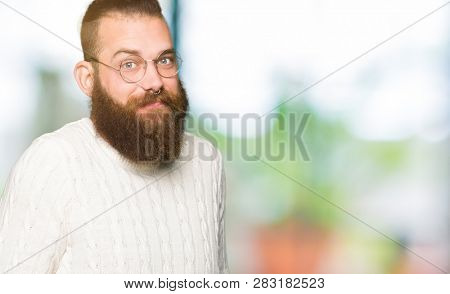 Young hipster man wearing glasses and winter sweater clueless and confused expression with arms and hands raised. Doubt concept.