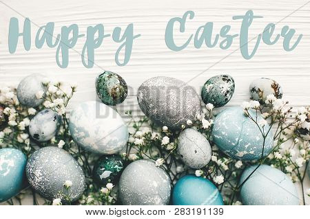 Happy Easter Text Sign On Stylish Easter Eggs With Spring Flowers On White Wooden Table. Modern East