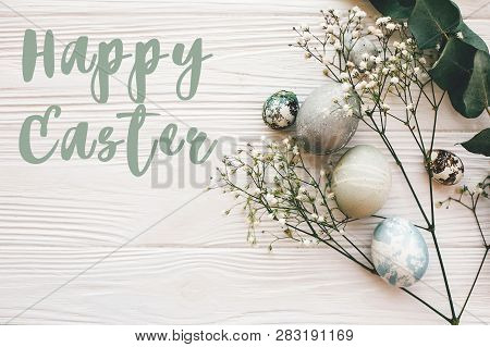 Happy Easter Text Sign On Stylish Easter Eggs With Spring Flowers And Green Branch On White Wooden T