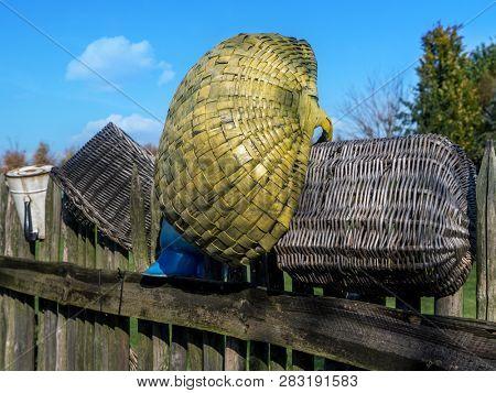 Old wicker baskets on farmstead wooden fence