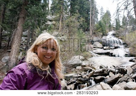 Blonde Hiker Poses By Whitney Portal Falls, A Waterfall Near The Trailhead For Mt. Whitney In Califo