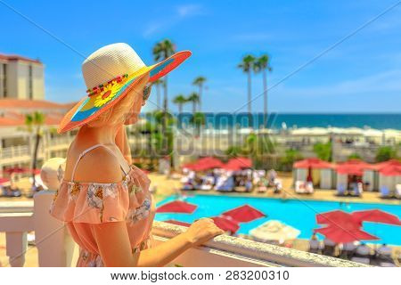 Portrait Of Tourist Woman In Hat At A Balcony Looking Scenic Landscape Of Pacific Ocean In Coronado