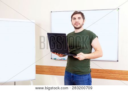 Portrait Of Informal Male Teacher In Classroom With Laptop Against The White School Board.