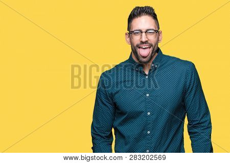 Young handsome business man wearing glasses over isolated background sticking tongue out happy with funny expression. Emotion concept.