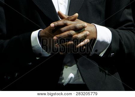 A Black Man In An Elegant Suit Clasp The Hands. Gestures And Features Of Business Negotiations. On A