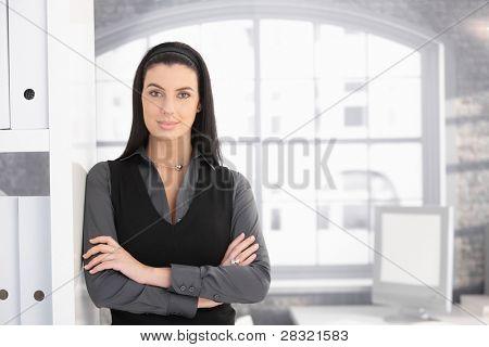 ¿Retrato de atractiva empresaria en oficina de pie con los brazos cruzados, sonriendo a la cámara.?