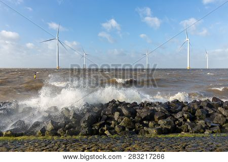 Dutch Sea With Off Shore Wind Turbines And Breaking Waves At The Shore