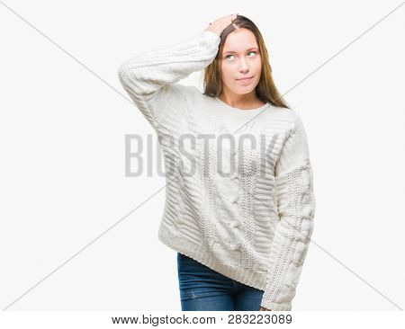 Young beautiful caucasian woman wearing winter sweater over isolated background confuse and wonder about question. Uncertain with doubt, thinking with hand on head. Pensive concept.