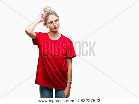 Young beautiful blonde woman wearing red t-shirt and glasses over isolated background confuse and wonder about question. Uncertain with doubt, thinking with hand on head. Pensive concept.