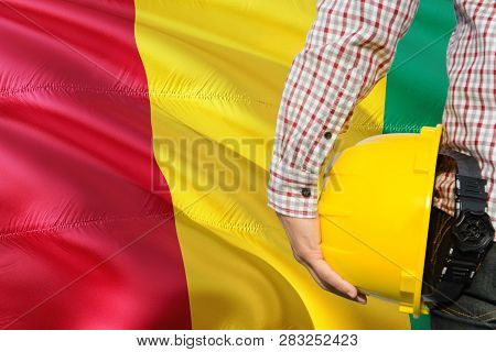 Guinean Engineer Is Holding Yellow Safety Helmet With Waving Guinea Flag Background. Construction An