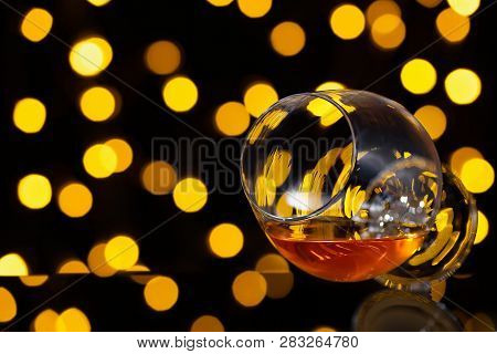 Brandy Or Cognac In Snifter Glass On Blurry Lights Background