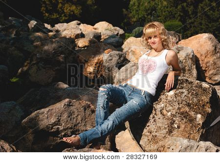 Lovely Girl Relaxing On The Rock