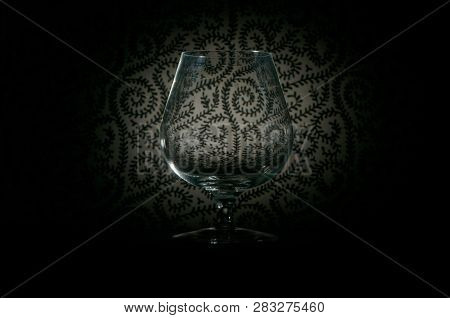 Empty Brandy Glass Highlighting A Fancy Design In Black And White In The Background Which Fades Into