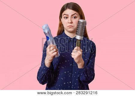 Studio Shot Of Puzzled Dark Haired Young Woman Holds Hairspray And Haircomb, Wears Fashionable Shirt