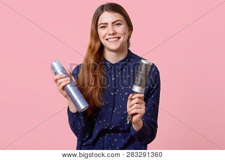 Hair care concept. Positive dark haired woman going to make coiffure, dressed in elegant shirt, smiles positively, poses over pink background, expresses happiness. Hairdresser fixes hair indoor poster