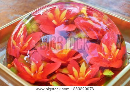 Half sphere jelly dessert with edible red flowers gelatin inside poster