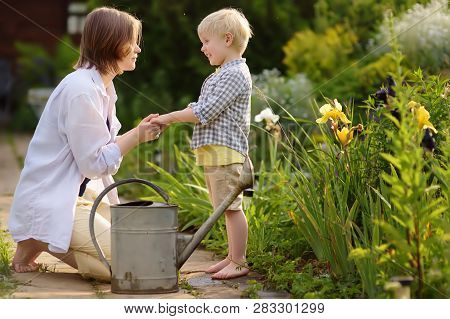 Beautiful Young Woman And Her Cute Son Watering Plants In The Garden At Summer Sunny Day. Gardening