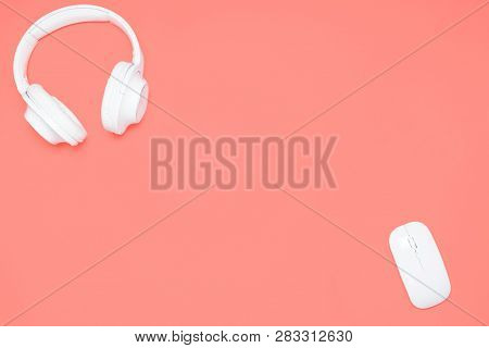 White Wireless Headphones And Wireless Mouse On Coral Colored Background. Top View. Flat Lay
