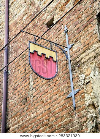 Metallic Plaque Of A Medieval Embattled Shield On A Brick Facade Of Asti, Piedmont, Italy.