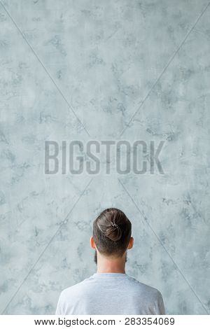 Think Different Concept. Man Backview. Copy Space On Grey Textured Background.