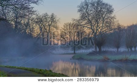 Sunrise In Winter In The Middle Of Nature With A Lake With Fog And Trees And A Path In Elsloo South