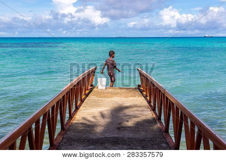 A Local Polynesian Boy Fishing From A Jetty Pier In A Tropical Azure Turquoise Blue Lagoon At Vaiaku