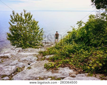 A man standing by the shore of Lake Ontario in Oakville, Ontari, Canada, staring out at the vast waters of the great lake deep in thought. poster