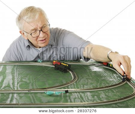 A senior man placing an engine on the track as he sets up a new N-gauge train set.  Focus is on the man.  On a white background.