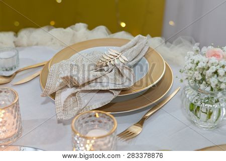 Golden napkin holder with olive branch, table set for an event party or wedding reception, luxury elegant table setting dinner