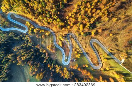 Winding Road In Autumn Forest At Sunset In Mountains. Aerial View. Top View Of Beautiful Asphalt Roa
