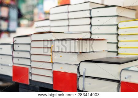 Bookstore Shelf With Pile Of New Books With Red Empty Plate. New Arrivals At Bookshop. Presentation