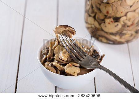 Mushrooms In Oil In Ceramic Bowl On White Wooden Background.