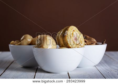 Mushrooms And Artichokes In Oil In Ceramic Bowl On White Wooden Background.