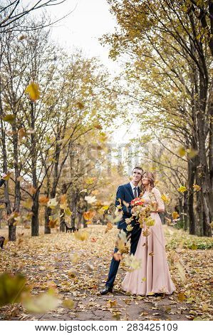 Smilng Newlyweds Hug Under A Fall Of Autumn Leaves
