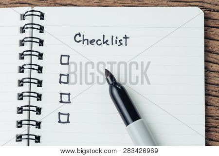 Checklist with marker pen and check box on small notepad on wood table, to do list, prioritize or reminder for project or plan. poster