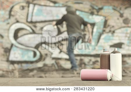 A Photography Of A Certain Number Of Paint Cans Against The Graf